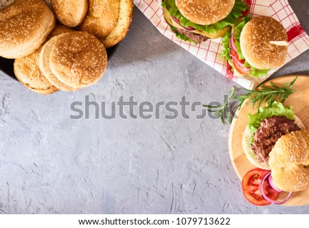 preparation of fresh tasty burgers. Green raw vegetables and buns on concrete background #1079713622
