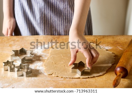 Preparation of ginger biscuits. A woman cuts out cookies as a star shape. Pastry cooking, homemade cuisine concept. stock photo