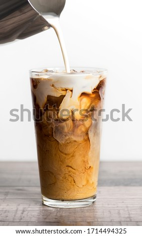 Preparation of iced coffee with milk or cream. Cold brew coffee. Iced latte with ice cube and milk