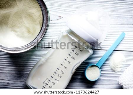 preparation of mixture baby feeding on wooden background top vie