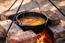 Preparation of raditional armenian pilaf in a cauldron on an open fire.
