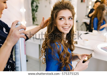 Preparation to celebrating in beauty salon of happy attractive model smiling to stylist. Beautiful coiffure, long curly brunette hair, cheerful mood, making hairstyle