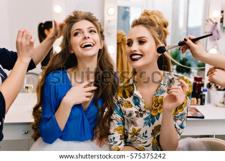 Preparation to great party of joyful young women in beauty salon. Expressing true posititve emotions, stylish look, fashionable models, beautiful coiffure, makeup, beauty service, stylist