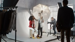 Preparations on a Backstage of the Photo Shoot: Make-up Artist Applies Makeup on Beautiful Black Model, Assistant Adjusts the Lightning Equipment. Fashion Magazine Studio Photoshoot