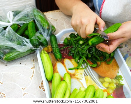prepare a salad. cleanses cucumber shells with women's hands. cucumber is cleaned with a peeling knife. Preparing for meals #1167302881