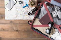 prepare accessories and travel items with map on wooden board, flat lay, top view background