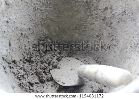 Prepare cement powder in a tank with a trowel for construction work. #1154031172