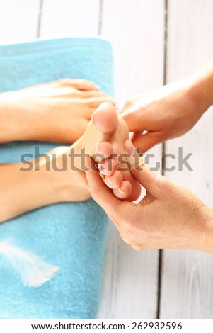 Prepare feet before the summer. Woman in a beauty salon for pedicure and foot massage.