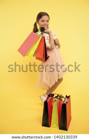 Prepare for school season buy supplies stationery clothes in advance. Great school shopping deals. Back to school season great time to teach budgeting basics children. Girl carries shopping bags.