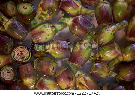 Prepared artichoke hearts floating in water for sale on a market stall #1222717429