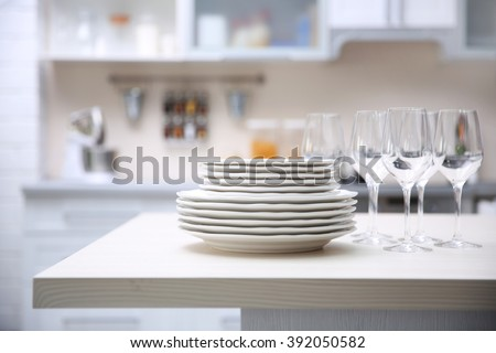 Prepared clean dishes for dinner party on a table in the kitchen