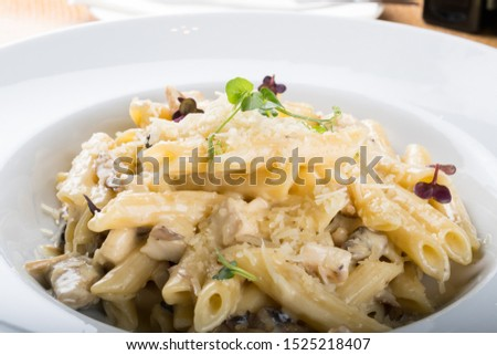 Prepared cooked penne pasta traditional italian dish with chicken and forest mushroom sauce, gratinated cheese with Taleggio parmesan and mozzarella shavings on top. Gluten free pasta healthy food.  Foto d'archivio ©