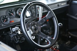 Prepared for racing & reconstructed drift sportcar interior, steering wheel in focus, close up view. Lots of gauges, gear shift knob, glove box blurred in the background. Chrome metal, black plastic.