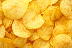 Prepared golden potato chips background. Top view