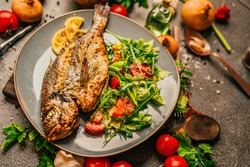 Prepared grilled gilthead sea bream.Fish diet meal.Seafood and vegetables for good health.Expensive dorado fish recipe.Healthy Mediterranean diet.Making fish barbecue.Grilled dorado with arugula salad