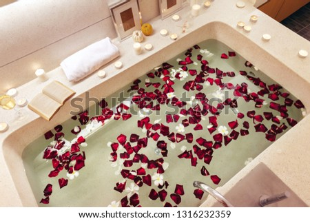 Prepared luxury spa bath decorated with flower petals and candles, top view from above.