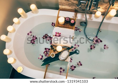 Prepared luxury spa bath decorated with flowers and candles, with wooden tray on it, top view from above