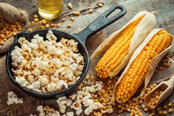 Prepared popcorn in frying pan, corn seeds in bowl and corncobs on kitchen table. Selective focus.