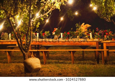 Prepared table for a rustic outdoor dinner at night with wineglasses, flowers and lamps in the garden