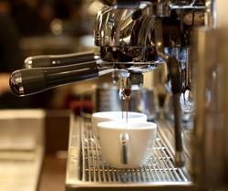 prepares espresso in his coffee shop; close-up