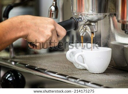 prepares espresso in his coffee shop with hand and close up