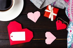 Preparing a gift for Valentine's Day. Red hearts, a cup of coffee and a small red gift tied with a white ribbon. View from above. Place for your text. Congratulations on the day of saint valentine.