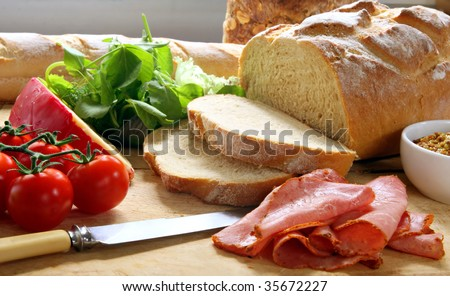 Preparing a sandwich, with fresh-sliced bread, cherry tomatoes, pastrami, cheese, lettuce,, and mustard, on chopping board.
