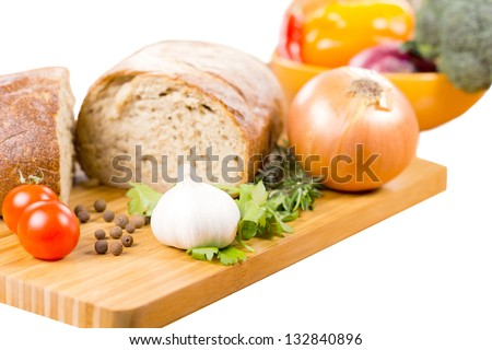 Preparing a savoury vegetarian meal with a fresh garlic, rosemary and parsley, cherry tomatoes, onion and bread on a wooden chopping board with a bowl of mixed vegetables in the background