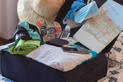 preparing a suitcase with summer clothes a mobile phone and money and several objects to protect oneself from the Covid19 like masks and gloves ready to make a trip around the world in summer