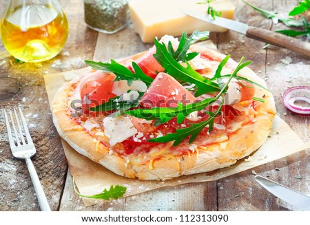 Preparing a tasty pizza in the kitchen using a crisp base topped with fresh herbs, ham, rucola, cheese and tomato
