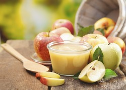 Preparing apple puree or sauce in a small glass jar with sliced apple pieces and a wooden spoon on an old wooden table outdoors