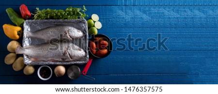 Preparing Brazilian Corvina Fish with Red Chili, Green Chili, Yellow Chili, Parsley, Potato, Black Olive, Onion, Italian Tomatoes and Lemon on the Navy Blue Wooden Table Stock fotó ©