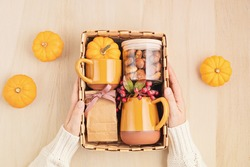 Preparing care package for thanksgiving, sasonal gift box with cup, tea or coffee package and cookies. Personalized eco friendly basket for fall holidays. Top view, flat lay