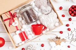 Preparing care package, seasonal gift box with coffee, candles and cup in red and white colors. Personalized eco friendly basket for family and friends for christmas. Top view, flat lay