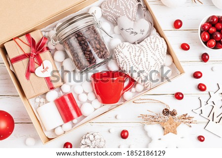 Preparing care package, seasonal gift box with coffee, candles and cup in red and white colors. Personalized eco friendly basket for family and friends for christmas. Top view, flat lay Stock photo ©