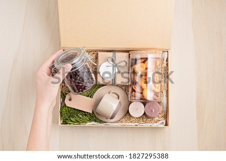 Preparing care package, seasonal gift box with coffee, cookies, candles and cup. Personalized eco friendly basket for family and friends for thankgiving, christmas, mothers and fathers day holidays.