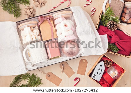 Preparing care package, seasonal gift box with marshmallow, tea,coffee or cacao box and christmas ornament. Personalized eco friendly basket for winter holidays. Top view, flat lay Stock photo ©