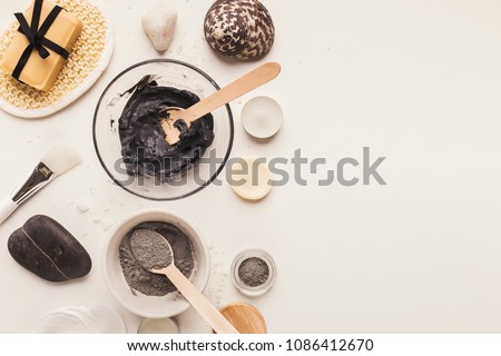 Preparing cosmetic black mud mask in glass bowl on white background. Top view of facial clay emulsion on table with spa products. Natural cosmetics for home or salon treatment, copy space
