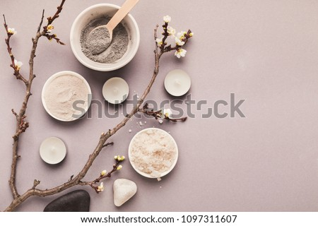 Preparing cosmetic black mud mask on gray background with tender flower. Natural cosmetics for home or salon spa treatment, top view, copy space