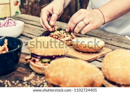 Preparing delicious burgers. Female hands cooking meat burgers with bacon, cheese and vegetables on wooden table. close up,selective focus, copy space