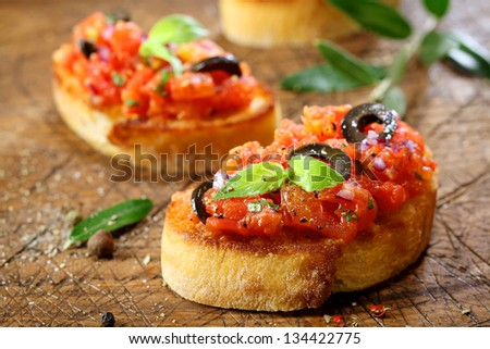 Preparing delicious Italian tomato bruschetta with chopped vegetables, herbs and oil on grilled or toasted crusty baguette sprinkled with seasoning and spices on an old grungy wooden chopping board