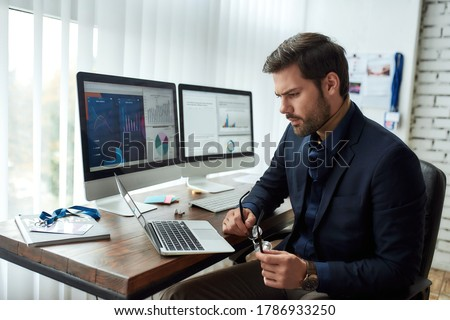 Preparing financial report. Young focused businessman or financial analyst sitting at his workplace in the office and working on laptop. Analyzing statistical data. Focus on man. Business, finance