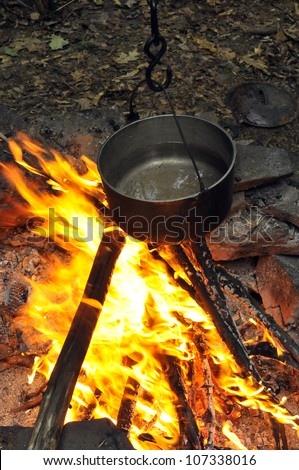 Preparing food on campfire in wild camping