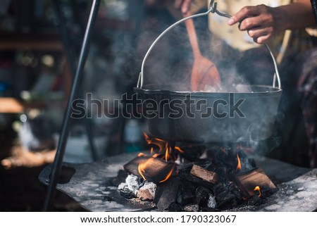 Preparing food on campfire in wild camping,Cooked food on a campfire on a camping trip. Camp kitchen, cooking food in the forest on fire. Frying pan on fire. Camping life concept.