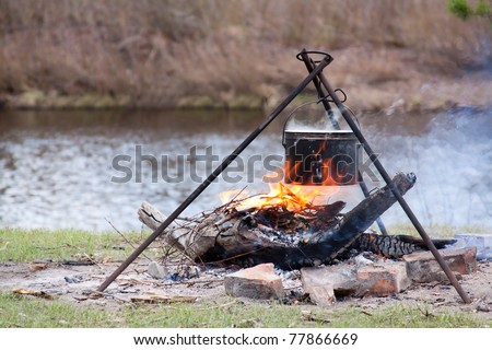 Preparing food on campfire in wild camping on pond background - stock photo