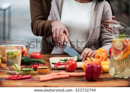 Preparing food together. Close-up of young couple cutting vegetables on the wooden table together