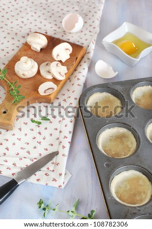 Preparing for baking mini quiches with mushrooms