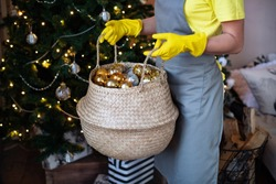 Preparing for Christmas. The girl holds in her hands a basket with New Year's decorations of gold color. Cleaning before the winter holidays. Christmas atmosphere