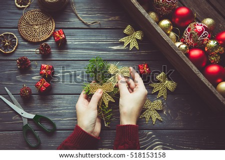 Preparing for Christmas.Vintage holiday decor in female hands on a wooden table.