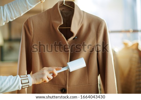 Photo of  Preparing for cold season. Closeup on housewife in white sweater cleaning coat on hanger with lint roller in the living room in sunny winter day.